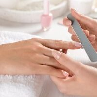 Manicurist filing client's nails at table, closeup. Spa treatment